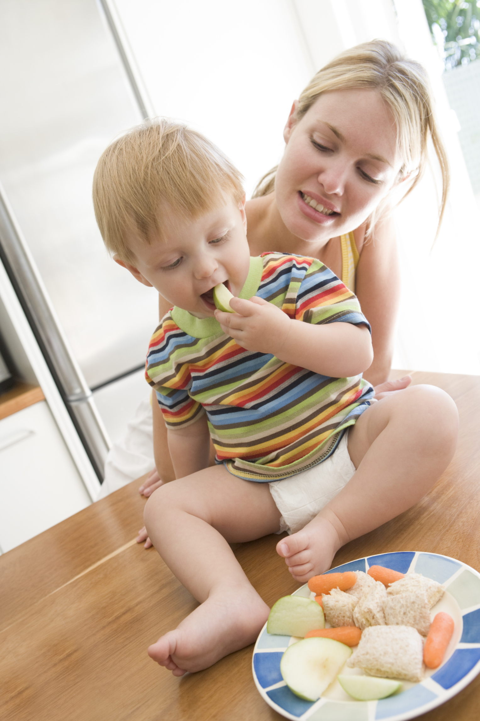 Mother and baby in kitchen eating fruit and vegeta